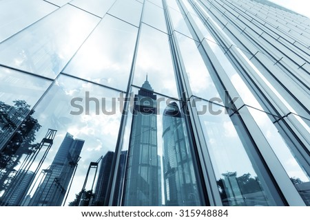 a skyscraper with glass walls and the reflection of landmarks on the opposite side - stock photo