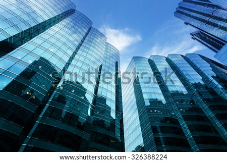 a skyscraper with glass walls and the reflection of landmarks on the opposite side