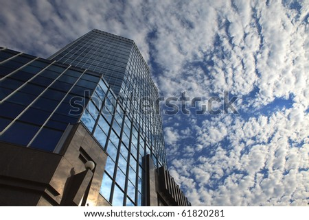 A skyscraper with the cloudy sky in the background, bottom view.