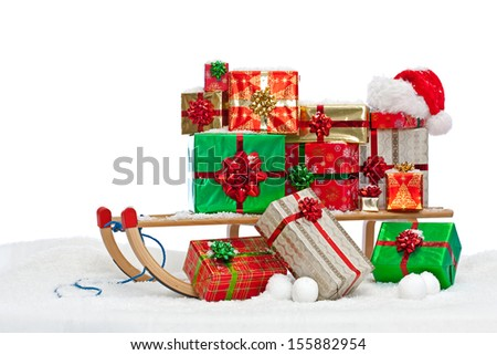 A sledge loaded with gift wrapped Christmas presents and a Santa hat, sitting on snow against a white background. - stock photo