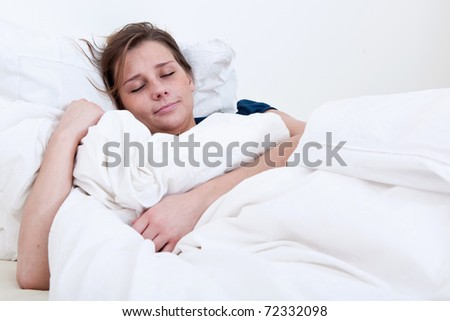 A sleeping girl lying in bed holding the blanket.