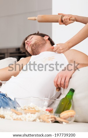 A sleeping lazy man being threatened by his wife with a rolling pin - stock photo
