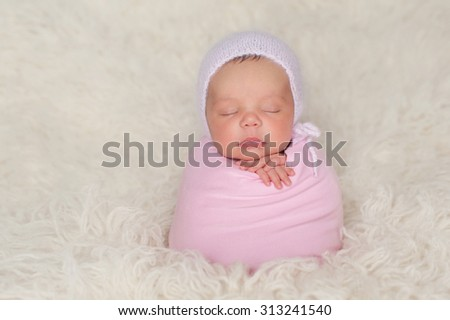 A sleeping nine day old newborn baby girl bundled up in a pink swaddle. She is propped up on a cream colored flokati (sheepskin) rug and wearing a knitted angora bonnet. - stock photo