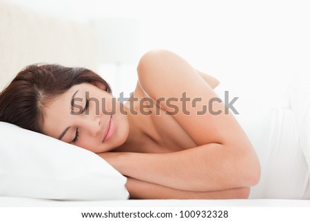 A sleeping woman is lying in bed with her head on the pillow and hands under it. - stock photo