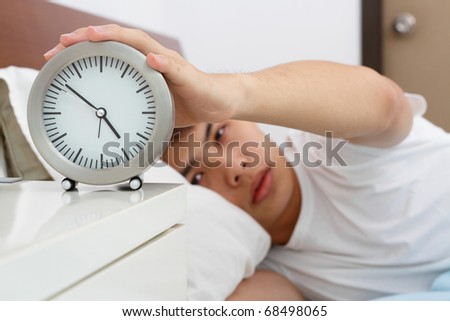 A sleepy Asian man switching off his alarm clock