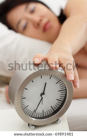 A sleepy Asian woman holding a table clock