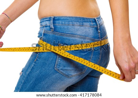 a slender young woman in jeans with a tape measure after a successful diet