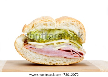 A slice of a Cuban sandwich with pickles, lettuce, spicy mayonnaise, cheese and meat.
