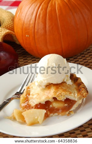 A slice of apple pie near a pumpkin table decoration - stock photo