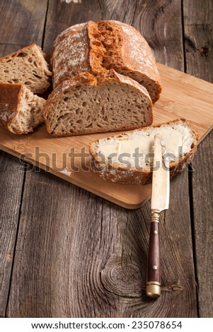A slice of bread with butter on a chopping board. Selective focus. - stock photo