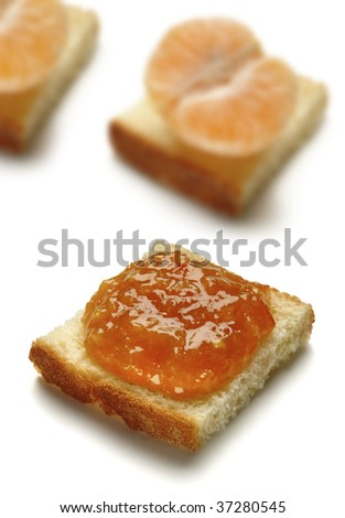 A slice of bread with Mandarin jam with slices of mandarin on the background - stock photo