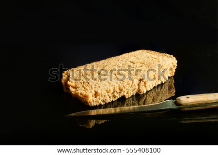 A slice of brown bread and a knife photographed in the studio on a black glass with reflection
