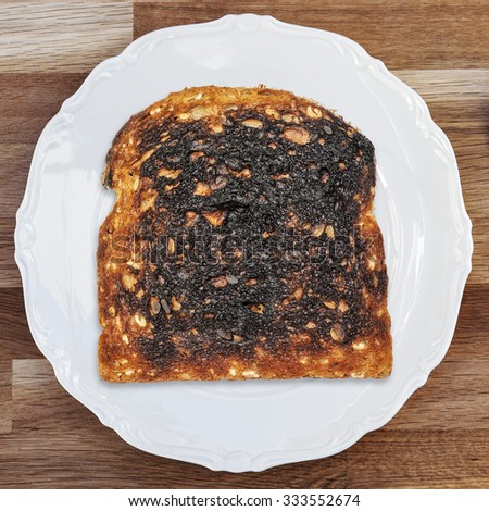 A slice of burnt toast on a shiny white plate placed upon a wooden table surface. - stock photo