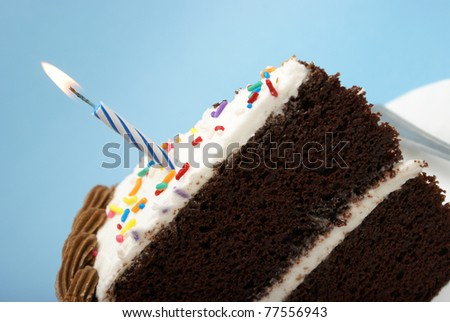 A slice of chocolate cake with a single lit candle. - stock photo