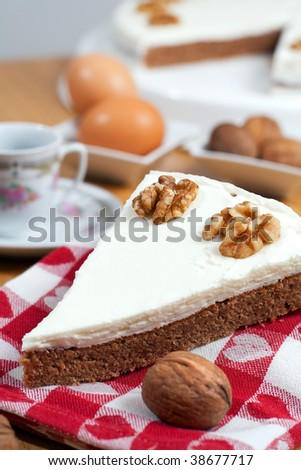 A slice of coffee and walnuts cake laid on a towel, surrounded by the ingredients on a wooden table