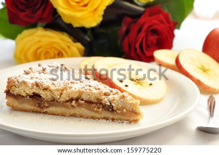 A slice of delicious apple pie with apple slices and roses in the back  - stock photo