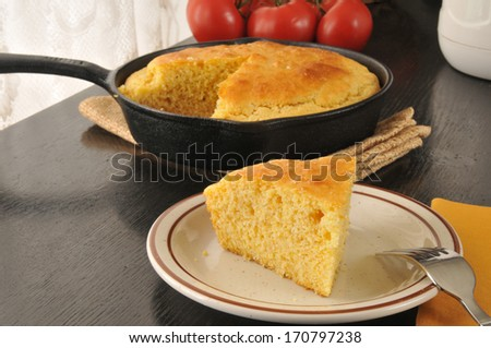 A slice of fresh baked cornbread cooked in a cast iron skillet - stock photo
