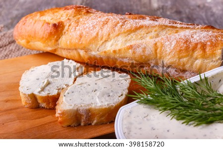 A slice of freshly baked baguette bread and healthy low fat cream cheese with dill and fresh green dill on wooden board. - stock photo