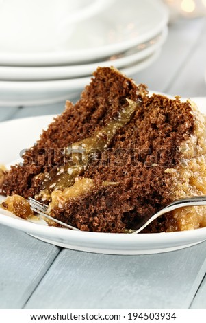 A slice of German chocolate cake on a plate. Shallow depth of field with selective focus on bite on the fork. - stock photo