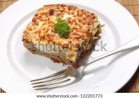 A slice of homemade lasagne verdi on a plate with a fork, high angle view