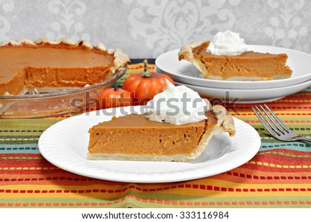 A slice of homemade pumpkin pie with whipped cream in front of a whole pumpkin pie. - stock photo