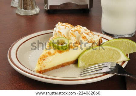 A slice of key lime pie with a glass of milk - stock photo