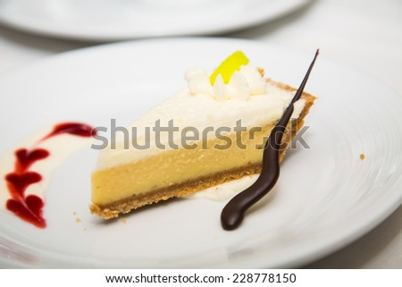 A slice of lemon meringue pie on a plate garnished with chocolate straw and raspberry syrup - stock photo
