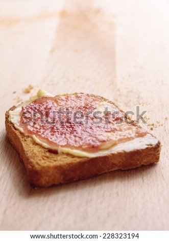 A slice of melba toast with butter and fruit jam on a wooden background - stock photo