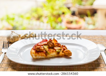 A slice of pizza on white plate ready to serve - stock photo
