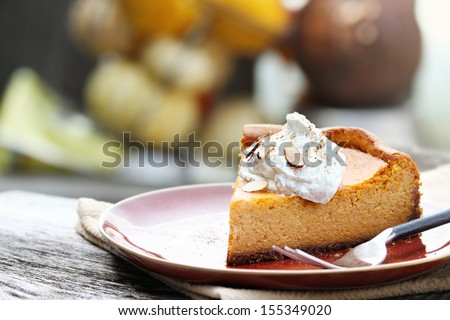 A slice of Pumpkin Cheesecake Pie with homemade whipped cream, almonds and pumpkin spice. Extreme shallow depth of field. - stock photo
