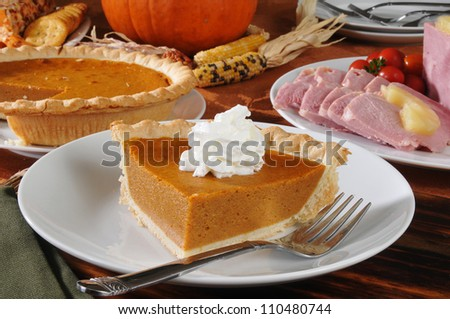 a slice of pumpkin pie on a Thanksgiving dinner table - stock photo
