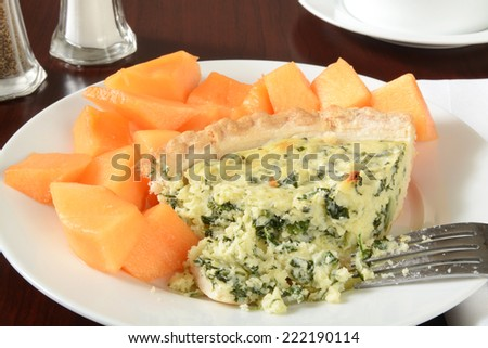 A slice of quiche Florentine with diced cantaloupe