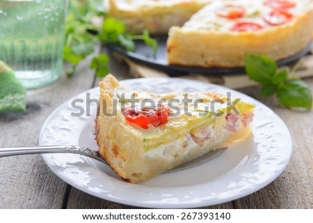 A slice of quiche with tomatoes and ham