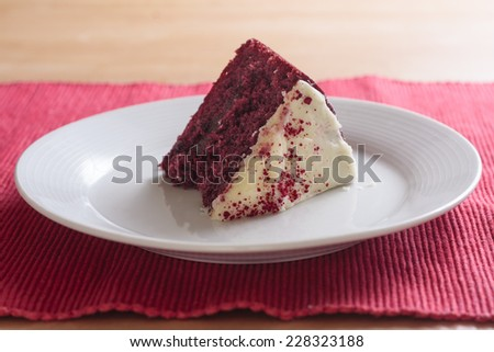 A slice of red velvet cake laying on it's side on a white plate - stock photo