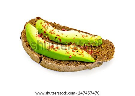 A slice of rye bread with avocado and pepper isolated on white background - stock photo