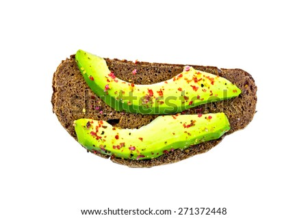 A slice of rye bread with slices of avocado and pepper isolated on white background top - stock photo