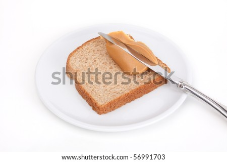A slice of wheat bread with a knife spreading a glob of peanut butter. White background. - stock photo