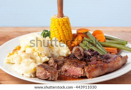 A sliced juicy rump steak cooked to medium, with mashed potatoes and vegetables - stock photo