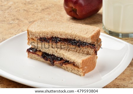 A sliced peanut butter and jelly sandwich with an apple and milk