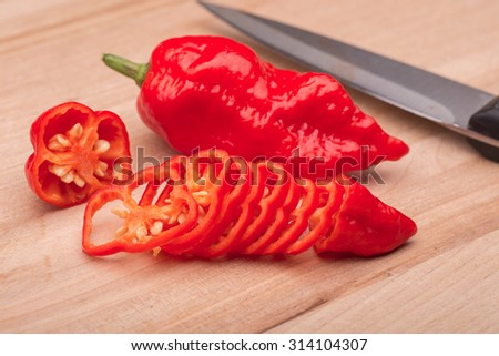 a sliced super hot ghost chili pepper on a wooden cutting board.