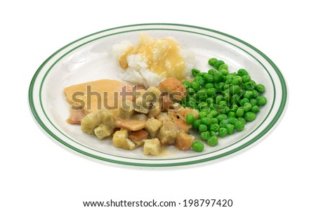 A sliced turkey in gravy with croutons, mashed potatoes and green peas on a plate. - stock photo
