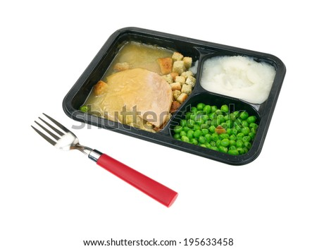 A sliced turkey in gravy with mashed potatoes and green peas TV dinner in black tray with red handled fork in the foreground.