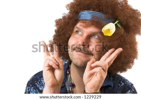 A slightly too old hippie making the peace sign with a tulip in his hair
