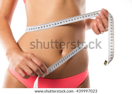 A slim girl measuring her waist, close-up.