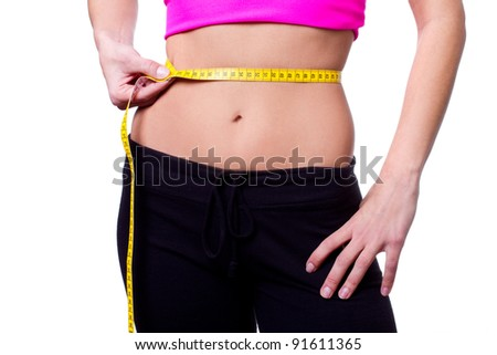 a slim girl measuring her waist - closeup, isolated on white background - stock photo