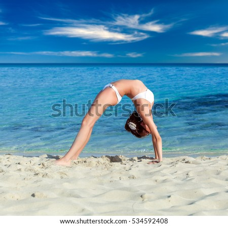 A slim woman is doing exercises on the beach