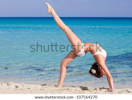 A slim woman is doing flexibility exercise on the beach