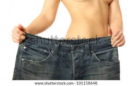 A slim woman is showing how much weight she lost - stock photo