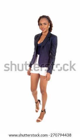 A slim young African American woman in white shorts and a grey jacket and high heels, standing isolated for white background.  - stock photo