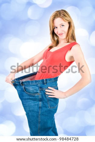 A slim young woman makes good diet   with blue lights in the background